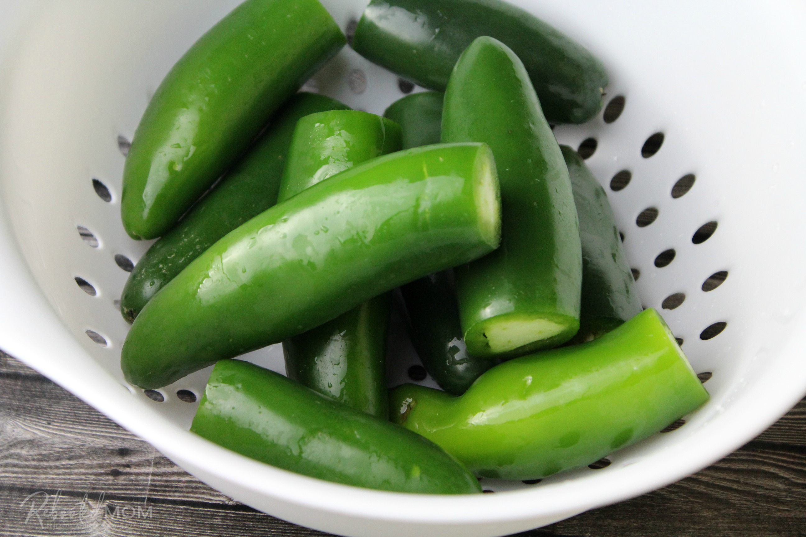 Whole jalapeño peppers in a colander