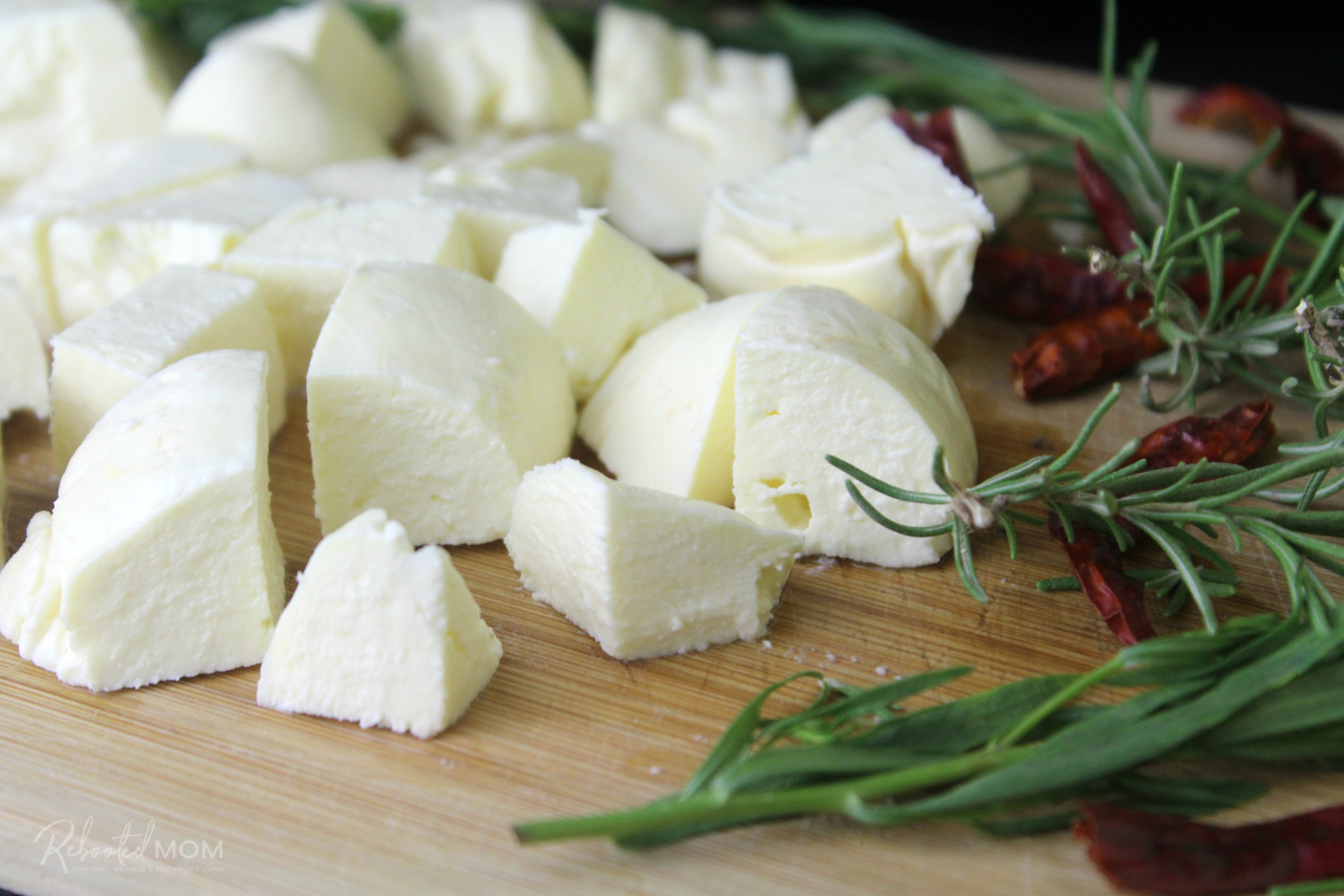 Homemade Feta Cheese on a Cutting Board with Fresh Herbs